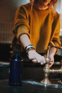 femme ouvrant le robinet avec de l'eau jaunâtre